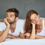 Shot of a young couple ignoring each other in the bedroom